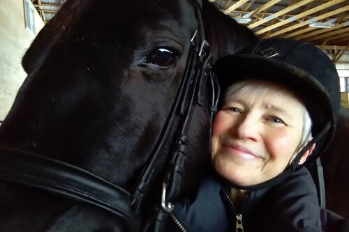 Woman pressing face against black horse